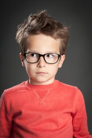 Serious surprised little boy wearing glasses. Studio shot portrait over gray background. Fashionable little boy. Banco de Imagens