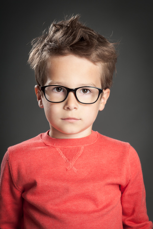five year old: Serious five year old boy wearing reading glasses. Studio shot portrait over gray background. Fashionable little boy.