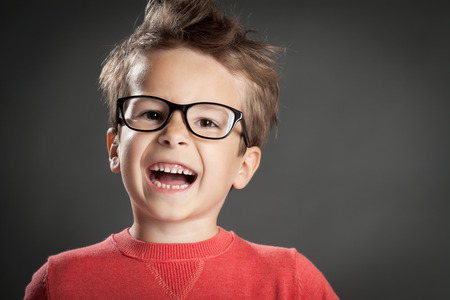 Happy enthousiastic boy. Studio shot portrait over gray background. Fashionable little boy. Standard-Bild