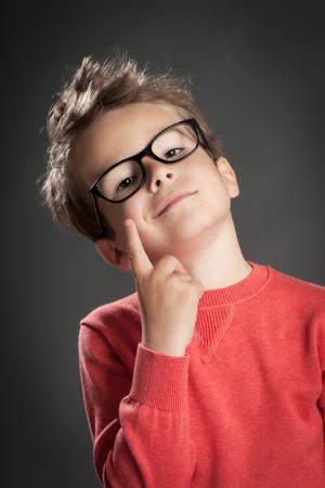 Smart nerdy jongetje in glazen. Studio opname portret over grijze achtergrond. Trendy kleine jongen. Stockfoto