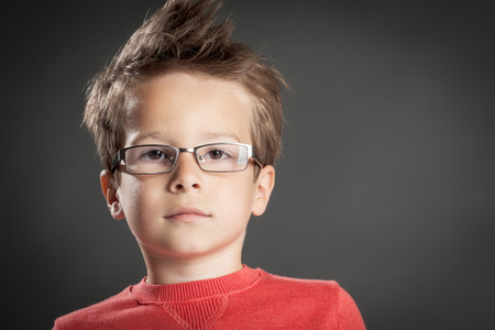 Serious little boy in glasses. Studio shot portrait over gray background. Fashionable little boy.
