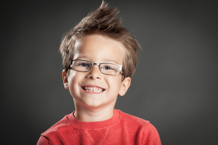 Happy little boy in glasses with toothy smile. Studio shot portrait over gray background. Fashionable little boy.