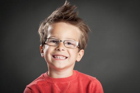 Glücklicher kleiner Junge in den Gläsern mit toothy Lächeln. Studio-Aufnahme Porträt über grauem Hintergrund. Modische kleine Junge.