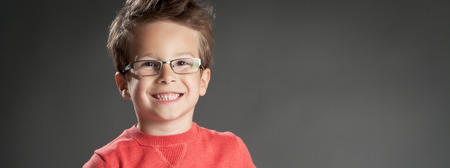 glasses eye: Happy little boy in glasses with toothy smile. Studio shot portrait over gray background. Fashionable little boy.