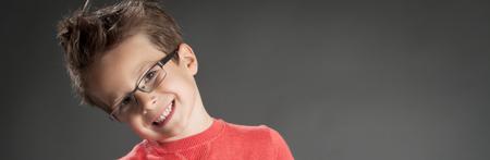 Heureux petit garçon dans des verres avec large sourire. Studio photo portrait sur fond gris. La mode petit garçon. Banque d'images - 44585660