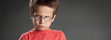 Angry little boy in glasses. Studio shot portrait over gray background. Fashionable little boy.