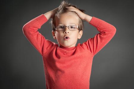 ojos marrones: Niño pequeño en gafas con expresión de sorpresa. Tiro del estudio retrato sobre fondo gris. niño de moda. Foto de archivo
