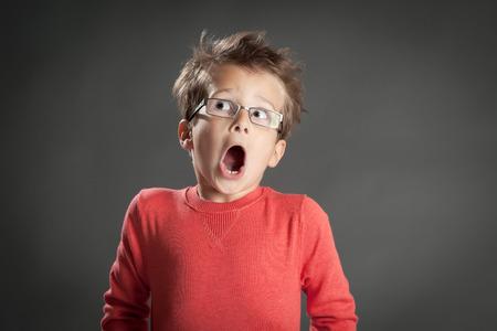 Bang en geschokt jongetje in glazen. Studio opname portret over grijze achtergrond. Trendy kleine jongen. Stockfoto