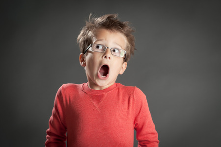 fear: Scared and shocked little boy in glasses. Studio shot portrait over gray background. Fashionable little boy.
