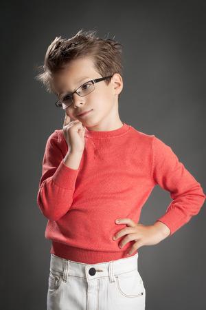 5 6 years: Pensive boy in glasses. Studio shot portrait over gray background. Fashionable little boy.