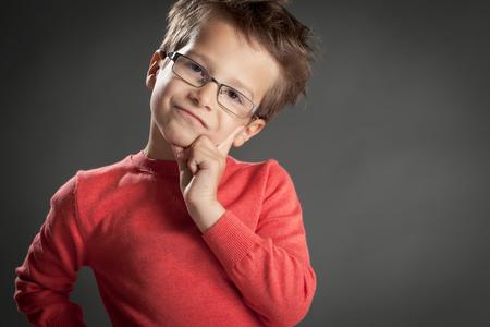 Sceptical five year old boy in glasses. Studio shot portrait over gray background. Fashionable little boy. Banco de Imagens