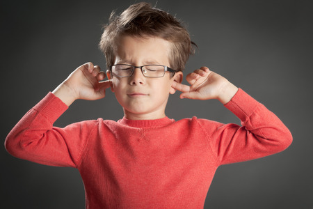 5 6 years: Little cute boy in glasses shutting his ears in denial. Studio shot portrait over gray background. Fashionable little boy.