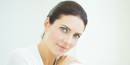 daylight: Beautiful natural European woman sitting in daylight at window with serene expresssion. Blue eyes and dark hair.