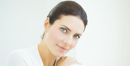 Mooie natuurlijke Europese vrouw zitten bij daglicht bij venster met serene expresssion. Blauwe ogen en donker haar.