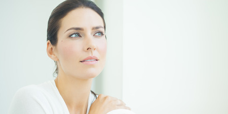 Beautiful natural European woman sitting in daylight at window with serene expresssion. Blue eyes and dark hair.