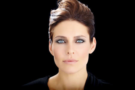 thirty: Beautiful elegant dramatic European woman with blue eyes and dark short hair over black background. Stock Photo