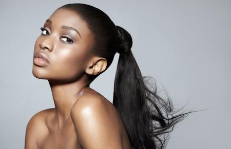 piel: Retrato de la hermosa niña africana serena sobre fondo gris de estudio. Belleza africana con el maquillaje y el pelo largo. Foto de archivo