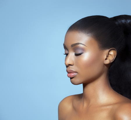 black women hair: Portrait of beautiful serene African girl with closed eyes over blue studio background. African beauty with makeup and long hair.