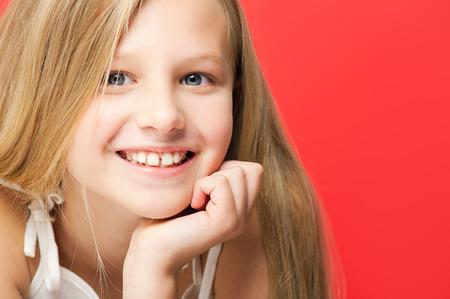 niños sonriendo: Retrato feliz sonriente niña de diez años en el estudio sobre fondo rojo. Foto de archivo