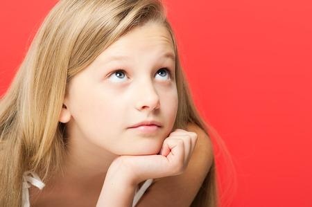 soñando: Bastante soñadora diez años retrato de la muchacha en estudio sobre fondo rojo.