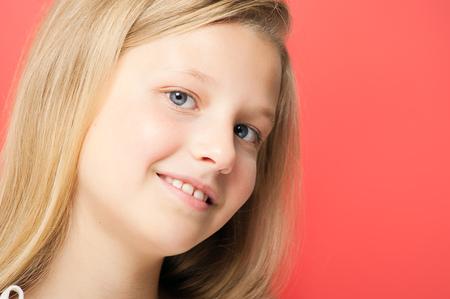 ten year old: Happy smiling ten year old girl portrait in studio over red background.
