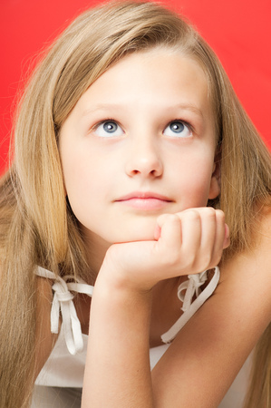 ten year old: Pretty dreamy ten year old girl portrait in studio over red background. Stock Photo
