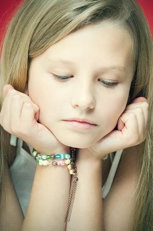 ten year old: Sad pensive ten year old girl portrait in studio over red background.