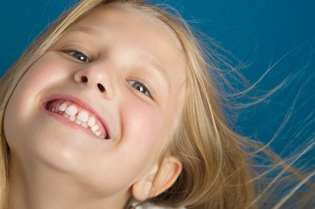 Happy ten year old girl closeup smiling with first healthy teeth.
