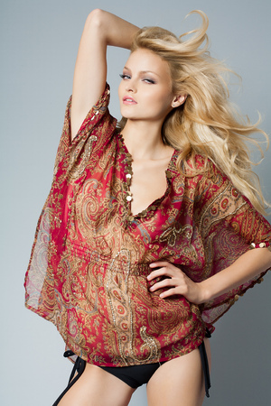 tunic: Beautiful woman with long blond hair posing in red silk tunic in studio over grey background.