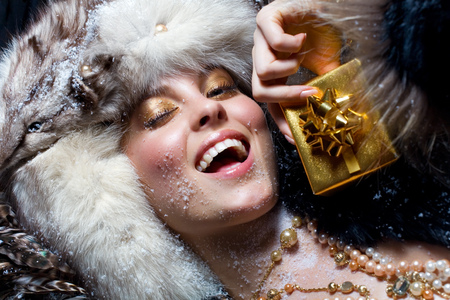 fashion photography: Woman in fur hat holding a little gift box and smiling.