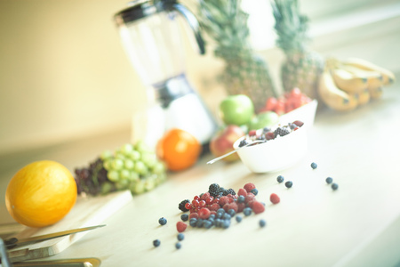 Ingredients for making smoothie in sunny kitchen. Variety of berries and fruit. Stock Photo