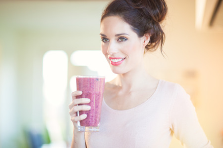 Young European woman drinking fresh berry smoothie in kitchen. Healthy eating concept. Full glass of healthy juice. Banco de Imagens