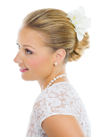 bridal makeup: Beautiful bride with makeup and gathered hairstyle posing over white background. Bridal makeup in pink tones.