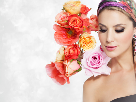 beautiful flowers: Beautiful woman portrait with glamour makeup and background decorated with artificial colorful flowers. Stock Photo