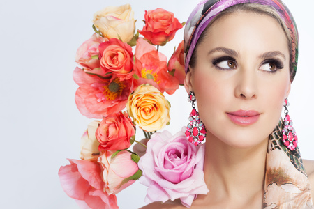 beautiful background: Beautiful woman portrait with glamour makeup and background decorated with artificial colorful flowers. Stock Photo
