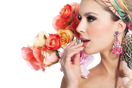 Retrato de la mujer hermosa con maquillaje de glamour y de fondo decorado con flores de colores artificiales. Foto de archivo