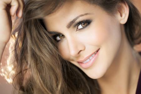 Eine Nahaufnahme Porträt einer jungen Frau glücklich mit schönen Augen. Mode und Beauty-Konzept im Studio.