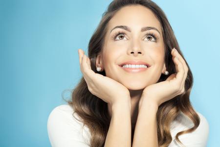 Gelukkig mooie jonge vrouw over blauwe achtergrond. Mode en beauty-concept in de studio. Stockfoto
