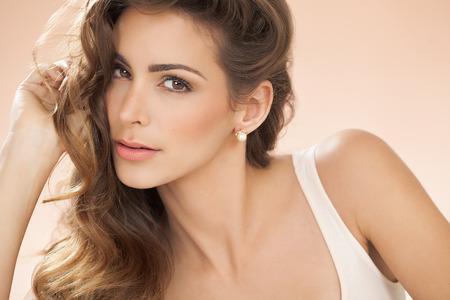 ojos marrones: Retrato de tonos cálidos de una mujer joven con el pelo marrón hermoso. La moda y el concepto de belleza en el estudio. Foto de archivo