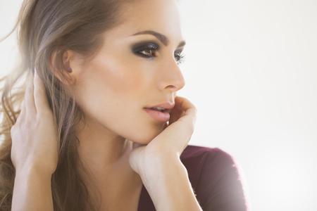 Portrait en plein jour d'une belle femme rêvé avec le maquillage des yeux de la mode. Mode et beauté concept studio.