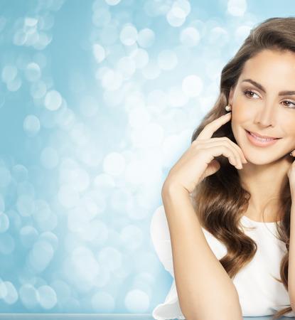 Jonge mooie vrouw met lang haar poseren en lachend over blauwe feestelijke glitter achtergrond. Mode en beauty-concept in de studio.