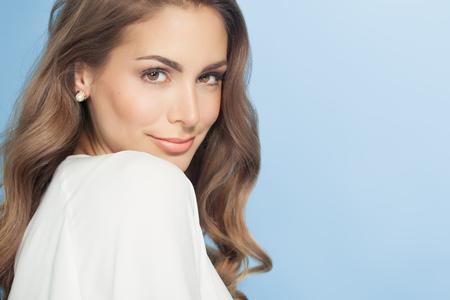 Junge schöne Frau mit langen Haaren posiert und über blauen Hintergrund lächelnd. Mode und Beauty-Konzept im Studio.