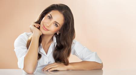 mujer elegante: Elegante, joven y profesional de la mujer hermosa que presenta en la mesa sobre fondo beige. La moda y el concepto de belleza en el estudio. Foto de archivo
