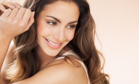 piel: Feliz hermosa mujer joven con el pelo largo sonríe sobre el fondo beige. La moda y el concepto de belleza en el estudio. Foto de archivo