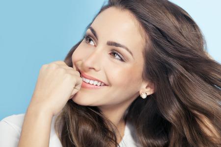 Felice donna sognante su sfondo blu. Moda e bellezza concetto in studio.