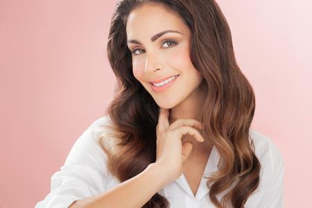 Mujer con el pelo lnog sonríe sobre el fondo de color rosa romántica delicada. La moda y el concepto de belleza en el estudio.