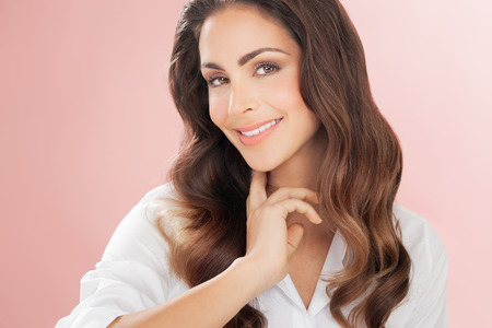 Smiling woman with lnog hair over delicate romantic pink background. Fashion and beauty concept in studio.