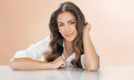 ojos marrones: Hermosa mujer joven sentado en la mesa sobre fondo caliente. La moda y el concepto de belleza en el estudio.