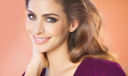smile face: Portrait of a beautiful smiling woman over beige background. Fashion and beauty concept in studio.