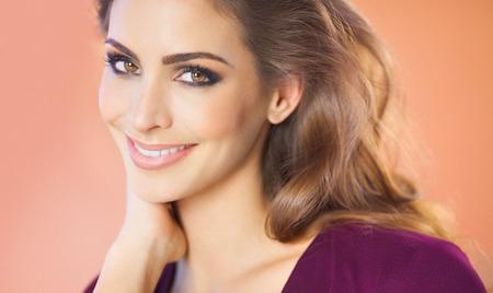 Portret van een mooie glimlachende vrouw over beige achtergrond. Mode en beauty-concept in de studio. Stockfoto